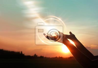 Fototapeta .Woman hands praying for blessing from god on sunset background