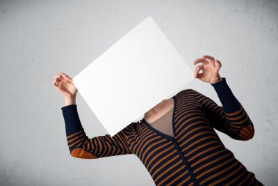 Fototapeta Woman holding in front of her head a paper with copy space