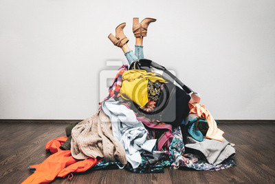 Fototapeta woman legs out of a pile of clothes on the floor. shopping addiction concept