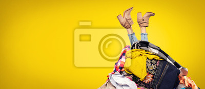 Fototapeta woman legs out of clothes pile on yellow background with copy space