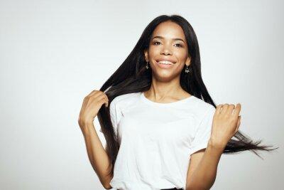 Fototapeta woman of african appearance in white t-shirt long hair Studio