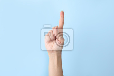 Fototapeta Woman showing number one on color background, closeup. Sign language