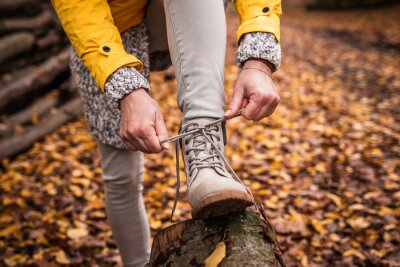 Fototapeta Woman tying shoelace on her hiking boot. Tourist is getting ready for autumn hike at forest trekking trail