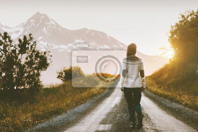 Fototapeta Woman walking alone on gravel road in mountains Travel lifestyle adventure vacations escape outdoor