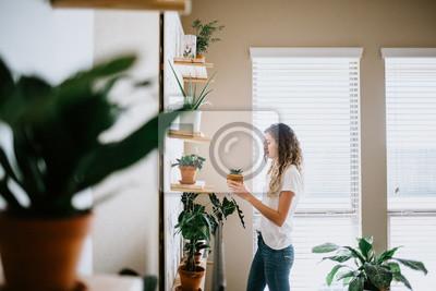 Fototapeta Woman with her Indoor Plants