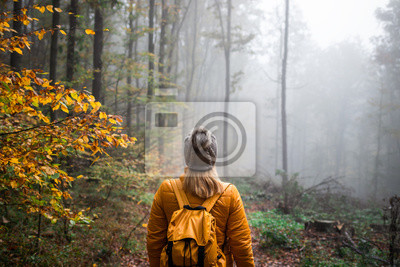 Fototapeta Woman with knit hat and backpack hiking in foggy woodland