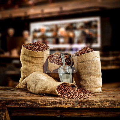 Wooden board of free space for your decoration and fresh coffee beans in brown sacks.