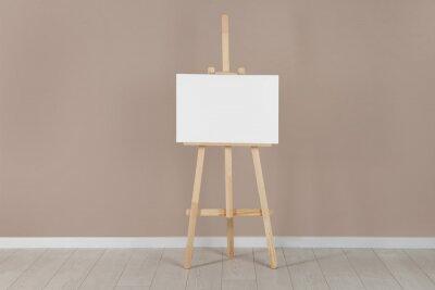 Fototapeta Wooden easel with blank canvas near beige wall