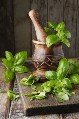 Fototapeta Wooden mortar and basil leaves on the table