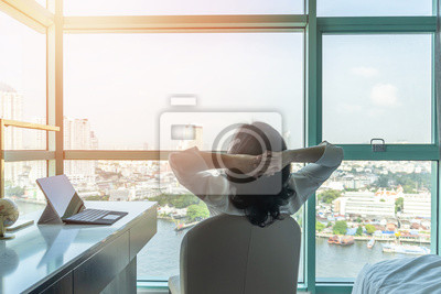 Fototapeta Work-life balance relaxation with Asian working business woman healthy lifestyle take it easy resting in comfort city hotel or home living room having good time with peace of mind, self-satisfaction