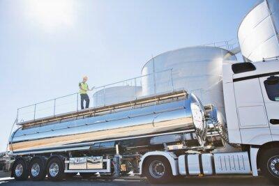 Fototapeta Worker on platform above stainless still milk tanker