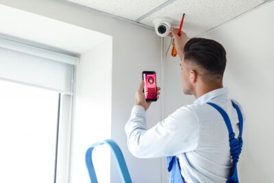 Fototapeta Worker with mobile phone checking alarm system indoors