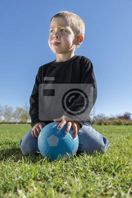 Wściekły dziecko gra w piłkę w parku