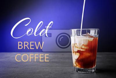 Wylewanie mleka w mrożonej kawie na szarym tle