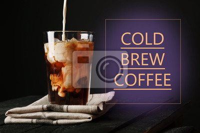 Wylewanie śmietany do szklanki z mrożoną kawę na serwetce i czarnym tle
