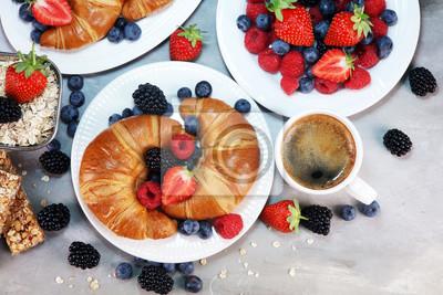 Wyśmienicie śniadanie z świeżymi croissants i dojrzałymi jagodami na starym marmurowym tle.