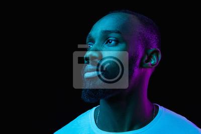Fototapeta Wysokiej mody samiec model w kolorowych jaskrawych neonowych światłach pozuje na czarnym tle.