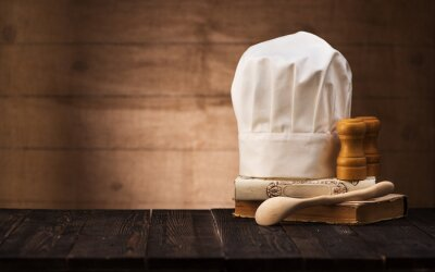 Fototapeta Chef's hat, vintage cookbooks and wooden spoon on the kitchen table with space for text.  cooking concept
