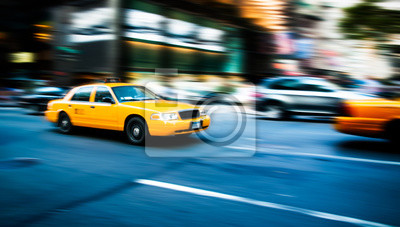 Fototapeta Yellow cab taxi traditional of New York City in fast movement with motion blur panning, in the busy streets of Manhattan, accelerating traffic moves during evening.