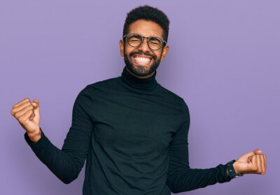 Fototapeta Young african american man wearing casual clothes very happy and excited doing winner gesture with arms raised, smiling and screaming for success. celebration concept.