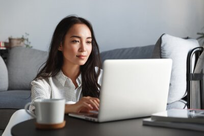 Fototapeta Young ambitious asian girl working remote from home, looking at laptop screen and smiling. Woman checking mail or researching while telecommuting, sitting on floor at her apartment