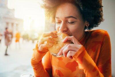Fototapeta Young beautiful multiethnic woman eating hamburger