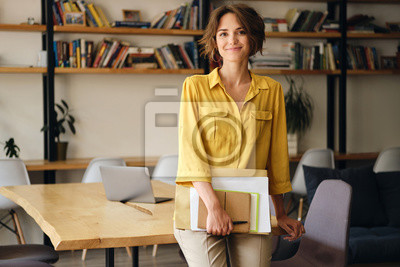 Fototapeta Young beautiful woman in yellow shirt leaning on desk with notepad and papers in hand while happily looking in camera in modern office