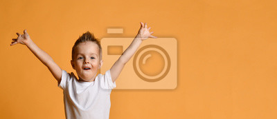 Fototapeta Young boy kid in white t-shirt celebrating happy smiling laughing with hands spreading up on yellow
