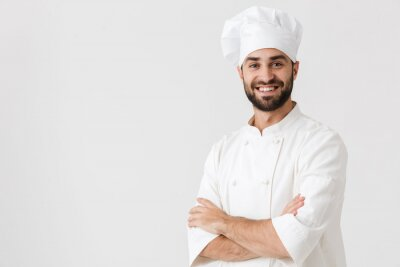 Fototapeta Young chef posing isolated over white wall background in uniform.