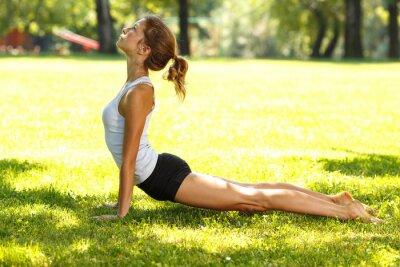 Fototapeta Young female doing yoga in nature.