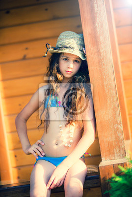 Fototapeta Young Girl in a swimsuit, hat and boom sitting on the railing of a bungalow on the coast
