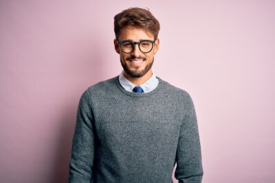 Fototapeta Young handsome man with beard wearing glasses and sweater standing over pink background with a happy and cool smile on face. Lucky person.