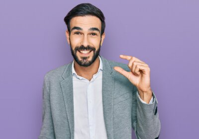 Fototapeta Young hispanic man wearing business clothes smiling and confident gesturing with hand doing small size sign with fingers looking and the camera. measure concept.