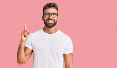 Fototapeta Young hispanic man wearing casual clothes and glasses showing and pointing up with finger number one while smiling confident and happy.