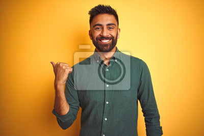 Fototapeta Young indian businessman wearing elegant shirt standing over isolated white background smiling with happy face looking and pointing to the side with thumb up.