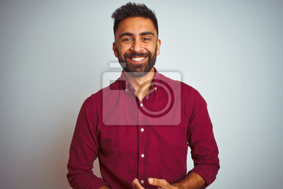 Fototapeta Young indian man wearing red elegant shirt standing over isolated grey background with hands together and crossed fingers smiling relaxed and cheerful. Success and optimistic