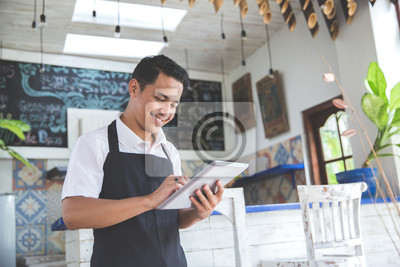 Fototapeta young male cafe owner with tablet