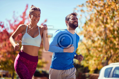 Fototapeta Young man and woman jogging at the park. healthy lifestyle.