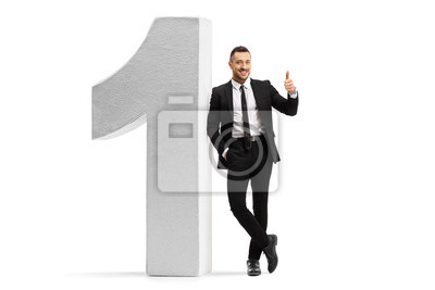 Fototapeta Young man in a black suit and tie leaning on number one and showing thumbs up