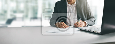 Fototapeta young man in suit writing business papers at desk in modern coworking office. copy space