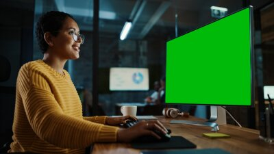 Fototapeta Young Multiethnic Specialist Working on Desktop Computer with Green Screen Mock Up Display in Creative Office. Beautiful Diverse Female Manager with Short Hair and Glasses is Wearing a Yellow Jumper.
