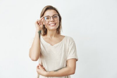 Young pretty girl smiling looking at camera correcting glasses over white background.