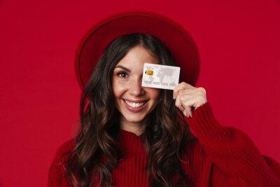 Fototapeta Young smiling woman wearing hat holding credit card