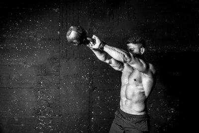 Fototapeta Young strong sweaty focused fit muscular man with big muscles holding heavy kettle bell for swing cross training hard core workout in the gym black and white