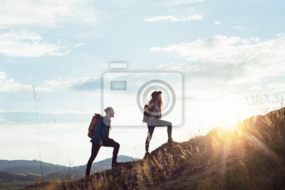 Fototapeta Young tourist couple travellers with backpacks hiking in nature.