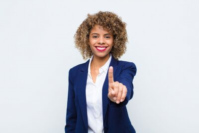 Fototapeta young woman african american smiling proudly and confidently making number one pose triumphantly, feeling like a leader against flat wall