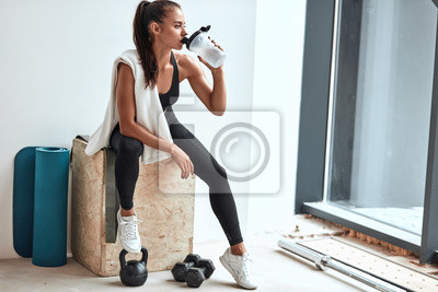 Fototapeta Young woman in leggins with towel on shoulders drinking water after fitness training