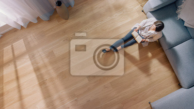 Fototapeta Young Woman is Sitting on a Floor and Reading a Book. Cozy Living Room with Modern Interior, Grey Sofa and Wooden Flooring. Top View Camera Shot.