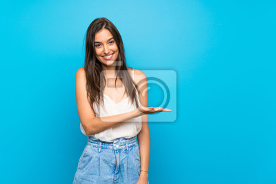 Fototapeta Young woman over isolated blue background smiling with a happy and pleasant expression