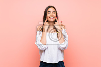 Fototapeta Young woman over isolated pink background smiling with a happy and pleasant expression